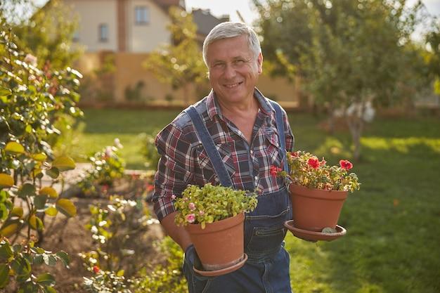 Zadowolony ogrodnik uśmiechający się, trzymający doniczki i stojący na zewnątrz w ogrodzie