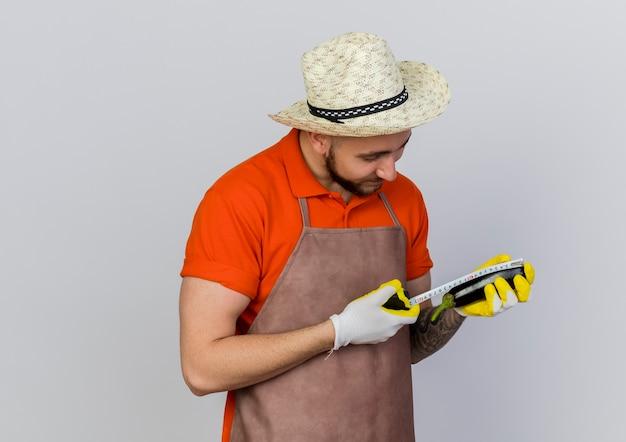 Zadowolony ogrodnik w kapeluszu ogrodniczym mierzy bakłażana centymetrem