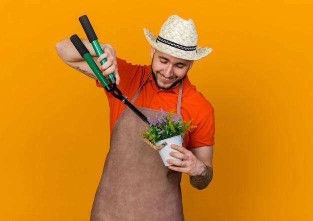 Zadowolony ogrodnik w kapeluszu ogrodniczym trzyma maszynkę do strzyżenia i udaje, że ściąga kwiaty w doniczce