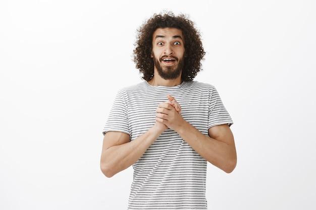Zadowolony, oszołomiony atrakcyjny facet ze wschodu z brodą i stylową kręconą fryzurą, trzymający splecione dłonie na piersi i gubiąc mowę z czegoś pozytywnego