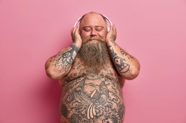 Zadowolony otyły grubas lubi słuchać ulubionej muzyki w słuchawkach stereo, pozuje z nagim brzuchem, ma wytatuowane ramiona i brzuch, ma nadwagę z powodu jedzenia fast foodów, odizolowany na różowej ścianie