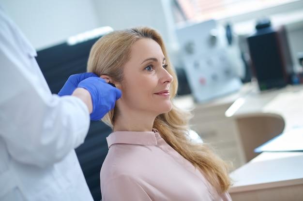 Zadowolony pacjent poddawany badaniu lekarskiemu w klinice słuchu
