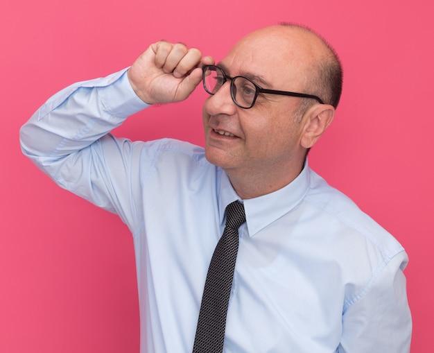 Zadowolony patrząc na bocznego mężczyznę w średnim wieku ubrany w białą koszulkę z krawatem i okularami na różowej ścianie
