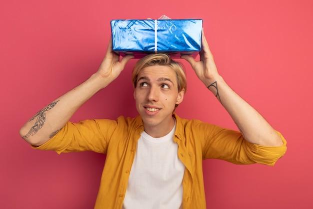 Zadowolony patrząc na bok młody blondyn ubrany w żółtą koszulkę trzyma pudełko na głowie na różowym tle