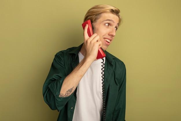 Zadowolony patrząc na bok młody blondyn w zielonej koszulce rozmawia przez telefon