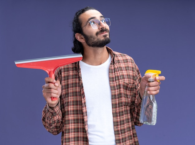Zadowolony patrząc na bok młody przystojny facet sprzątający na sobie t-shirt, trzymając głowę mopa z butelką z rozpylaczem na białym tle na niebieskiej ścianie