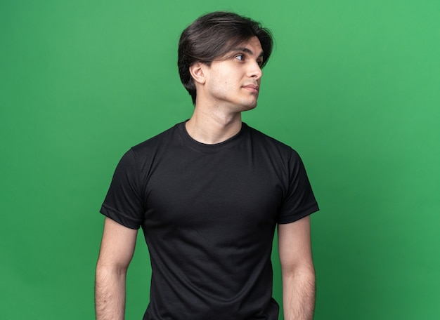 Zadowolony patrząc na bok młody przystojny facet ubrany w czarną koszulkę odizolowaną na zielonej ścianie z kopią przestrzeni