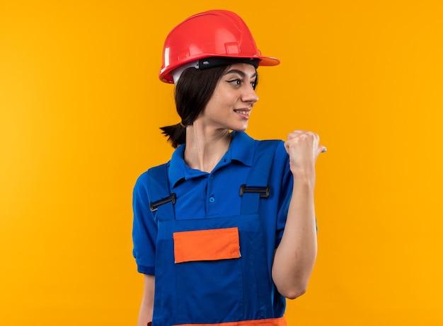 Zadowolony, patrząc na młodą kobietę budowniczego w jednolitych punktach za odizolowaną na żółtej ścianie z kopią miejsca