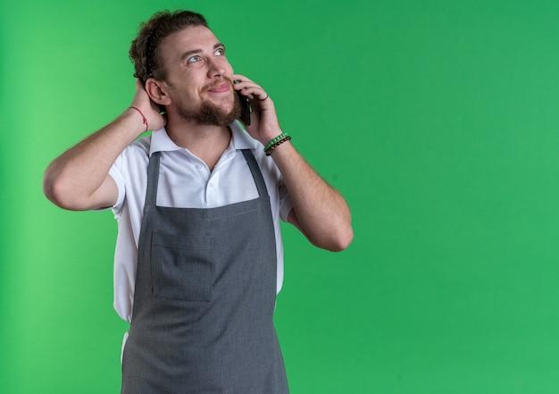 Zadowolony, patrząc na młodego fryzjera męskiego, noszącego mundur, rozmawiającego przez telefon i kładącego rękę na głowie, odizolowanej na zielonej ścianie