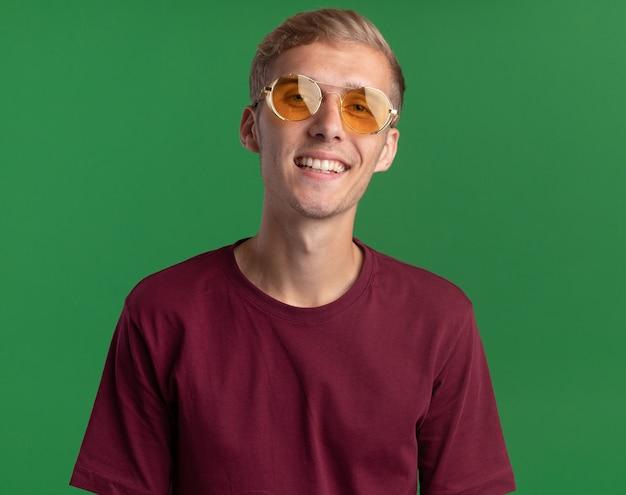 Zadowolony patrząc na przód młody przystojny facet ubrany w czerwoną koszulę i okulary na białym tle na zielonej ścianie