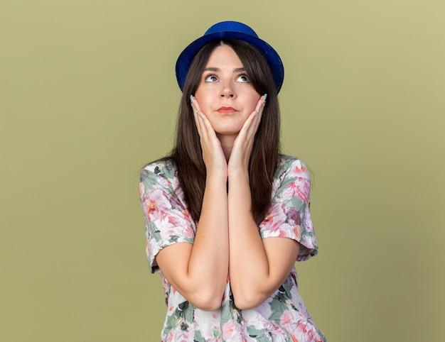 Zadowolony, patrząc w górę, młoda piękna dziewczyna w imprezowym kapeluszu, kładąc ręce na policzkach