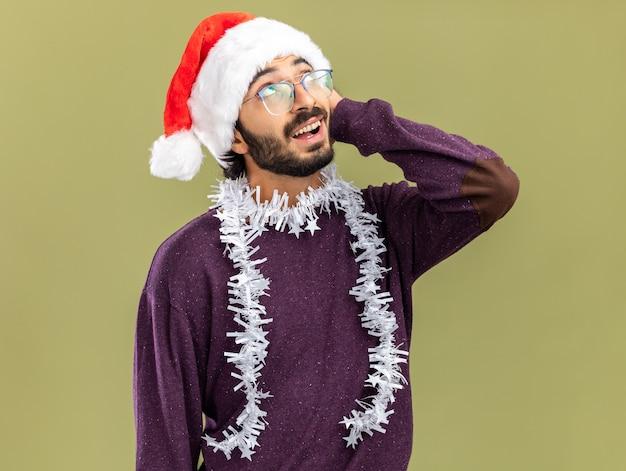 Zadowolony patrząc w górę młody przystojny facet noszący świąteczny kapelusz z girlandą na szyi, kładący rękę na głowie odizolowany na oliwkowozielonej ścianie