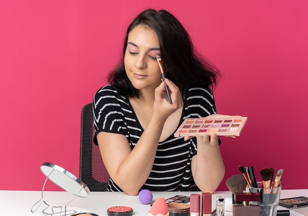 Zadowolony patrząc w lustro młoda piękna dziewczyna siedzi przy stole z narzędziami do makijażu, nakładającymi cień do powiek z pędzlem do makijażu na różowej ścianie