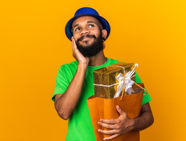 Zadowolony, patrząc z boku, młody afro-amerykański facet w kapeluszu imprezowym, trzymający torbę z prezentami pokrytą policzkiem ręką odizolowaną na pomarańczowej ścianie
