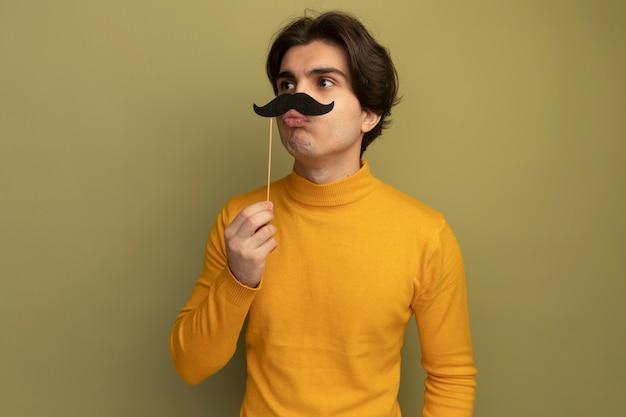 Zadowolony patrząc z boku młody przystojny facet ubrany w żółty sweter z golfem, trzymający fałszywe wąsy z kijem odizolowany na oliwkowej ścianie