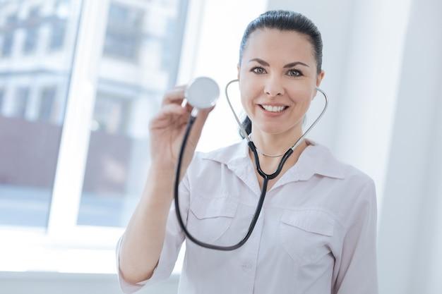 Zadowolony, pewny siebie lekarz pracujący w szpitalu, demonstrując stetoskop i wyrażając pozytywne nastawienie