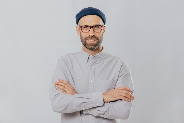 Zadowolony, pewny siebie męski projektant nosi stylowe nakrycia głowy, ubrany w białą koszulę, trzyma założone ręce
