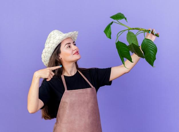 Zadowolony piękny ogrodnik dziewczyna w mundurze na sobie kapelusz ogrodniczy podnoszący i wskazuje na roślinę na białym tle na niebieskim tle