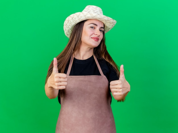 Zadowolony piękny ogrodnik dziewczyna w mundurze na sobie kapelusz ogrodniczy pokazujący kciuki do góry na białym tle na zielono