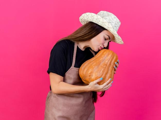 Zadowolony piękny ogrodnik dziewczyna w mundurze na sobie kapelusz ogrodniczy trzymając i całując dyni na różowym tle