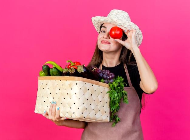 Zadowolony piękny ogrodnik dziewczyna w mundurze na sobie kapelusz ogrodniczy trzymając kosz warzyw i pokazując gest spojrzenia z pomidorem na białym tle na różowym tle