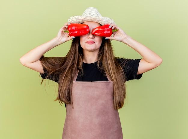 Zadowolony piękny ogrodnik dziewczyna w mundurze na sobie kapelusz ogrodniczy trzymając paprykę na oczach na białym tle na oliwkowym tle