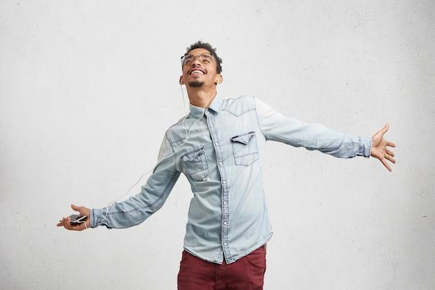 Zadowolony, podekscytowany mężczyzna nosi modne ciuchy, słucha radosnych piosenek na smartfonie ze słuchawkami,