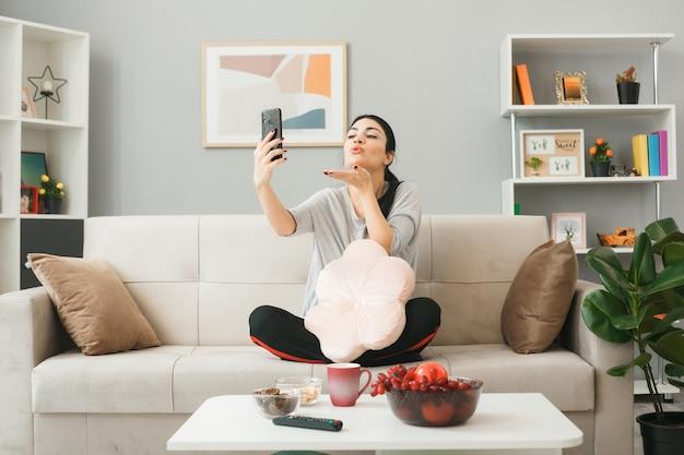 Zadowolony pokazując gest pocałunku młoda dziewczyna trzyma poduszkę i patrząc na telefon, siedząc na kanapie za stolikiem kawowym w salonie