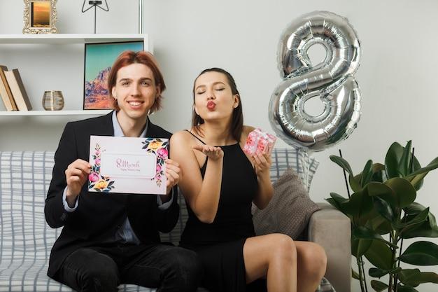 Zadowolony pokazując gest pocałunku młoda para na szczęśliwy dzień kobiet trzymając kartkę z życzeniami z obecnym siedzeniem na kanapie w salonie
