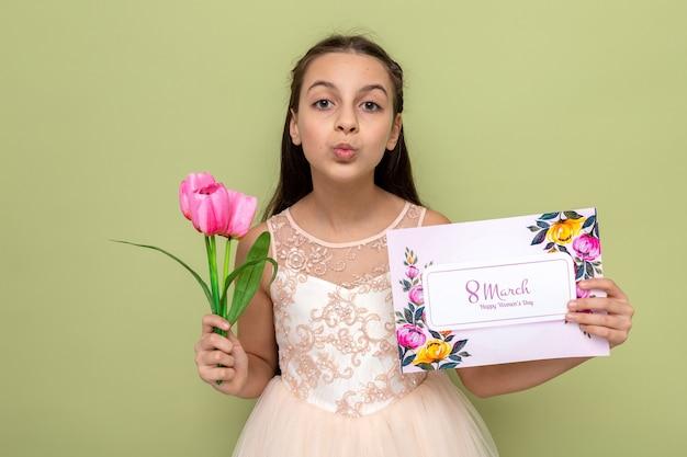 Zadowolony pokazując gest pocałunku piękna mała dziewczynka na szczęśliwy dzień kobiety trzymająca kwiaty z pocztówką odizolowaną na oliwkowozielonej ścianie