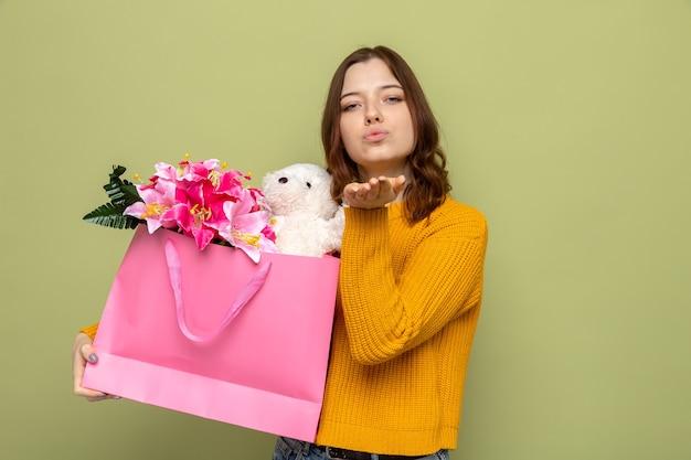 Zadowolony pokazując gest pocałunku piękna młoda dziewczyna na szczęśliwy dzień kobiety trzymająca torbę na prezent odizolowaną na oliwkowozielonej ścianie
