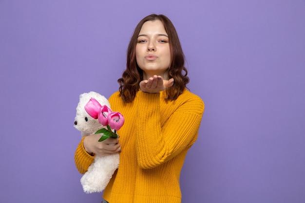 Zadowolony pokazując gest pocałunku piękna młoda dziewczyna trzyma kwiaty z misiem