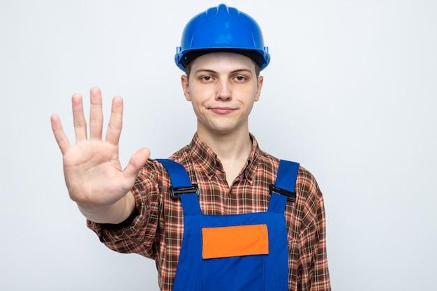 Zadowolony pokazując gest zatrzymania młodego budowniczego płci męskiej w mundurze