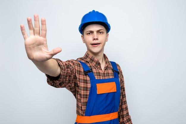 Zadowolony pokazując gest zatrzymania młodego męskiego budowniczego noszącego mundur