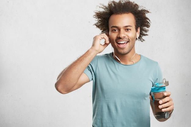 Zadowolony pozytywny mężczyzna z zarostem uśmiecha się radośnie, słucha muzyki w słuchawkach