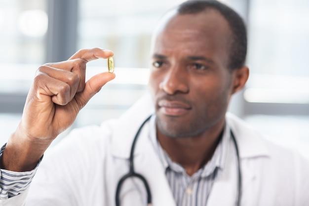 Zadowolony pracownik medyczny podnoszący rękę, demonstrujący małą tabletkę