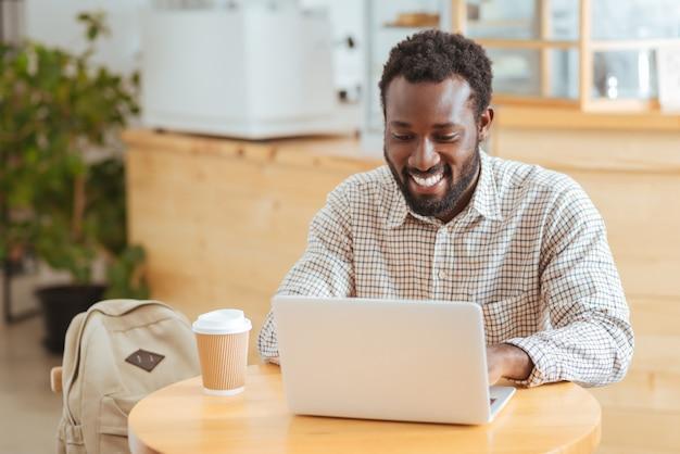 Zadowolony pracownik. uroczy młody człowiek siedzi przy stole w kawiarni i pracuje na laptopie, uśmiechając się