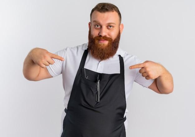 Zadowolony profesjonalny brodaty fryzjer w fartuchu, wskazując na siebie zadowolonego stojącego nad białą ścianą