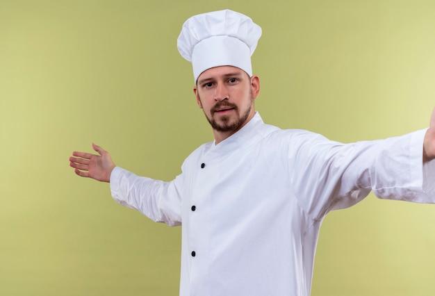 Zadowolony profesjonalny kucharz mężczyzna w białym mundurze i kapeluszu kucharz wygląda pewnie, wykonując powitalny gest z rękami stojącymi na zielonym tle