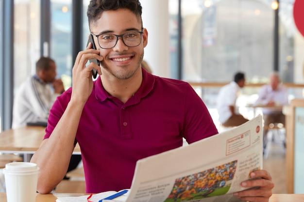 Zadowolony przedsiębiorca o wesołym wyrazie twarzy, nosi okulary optyczne, prowadzi rozmowę telefoniczną, czyta gazetę, omawia wiadomości z przyjacielem, pije kawę w przytulnej restauracji. profesjonalny freelancer