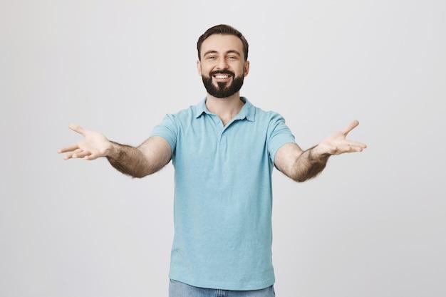 Zadowolony, przyjacielski mężczyzna zaprasza do siebie, rozłożone ręce witające