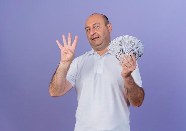 Zadowolony przypadkowy dojrzały biznesmen trzyma pieniądze i pokazuje cztery ręką na białym tle na fioletowym tle z miejsca na kopię