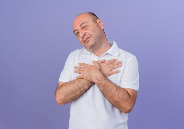 Zadowolony przypadkowy dojrzały biznesmen trzymając ręce skrzyżowane na klatce piersiowej na białym tle na fioletowym tle z miejsca na kopię