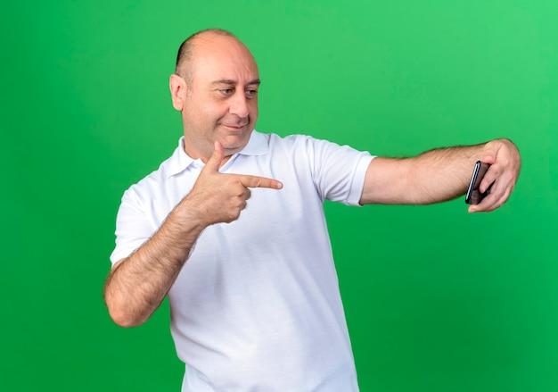 Zadowolony przypadkowy dojrzały mężczyzna bierze selfie i wskazuje na telefon na białym tle na zielonym tle