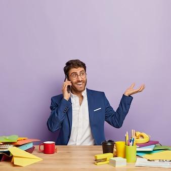 Zadowolony przystojny biznesmen siedział przy biurku