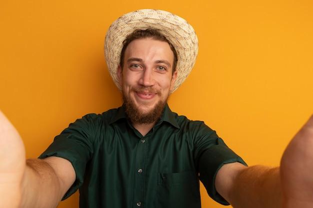 Zadowolony przystojny blondyn w kapeluszu plażowym udaje, że trzyma przód odizolowany na pomarańczowej ścianie