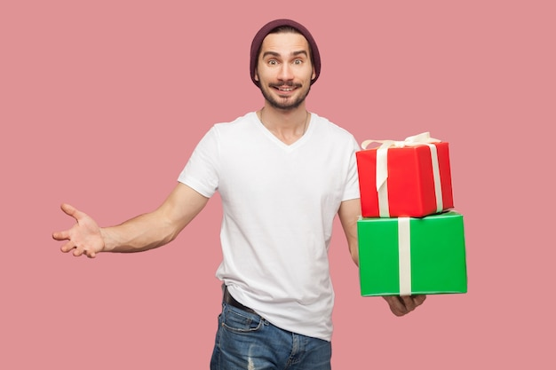 Zadowolony przystojny brodaty młody hipster mężczyzna w białej koszuli i dorywczo kapelusz stojący, trzymając dwa obecne pudełko z podniesionymi rękami, patrząc na kamery. wewnątrz, na białym tle, studio strzał, różowe tło