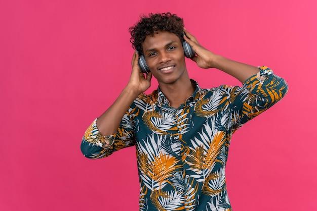 Zadowolony przystojny ciemnoskóry mężczyzna z kręconymi włosami w koszulce z nadrukiem liści w słuchawkach, słuchający muzyki na różowym tle