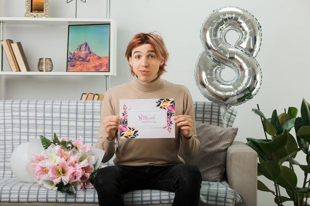 Zadowolony przystojny facet w szczęśliwy dzień kobiet, trzymając kartkę z życzeniami, siedząc na kanapie w salonie