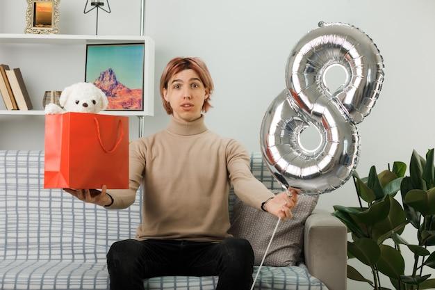 Zadowolony przystojny facet w szczęśliwy dzień kobiet trzymający balon numer osiem z torbą na prezenty, siedzący na kanapie w salonie